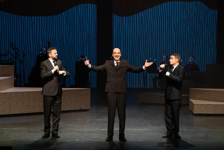 Fotografia przedstawia trzech mężczyzn ubranych w czarne garnitur. Mężczyzna stojący w środku z uśmiechem na twarzy trzyma podniesione ramiona w geście powitania, dwóch pozostałych mężczyzn stojących po bokach patrzy na niego ze zdziwieniem. Każdy z nich trzyma mikrofon. Za ich plecami widać zespół muzyczny grający na instrumentach.