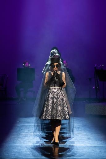 Fotografia przedstawia kobietę w ciemnych okularach, czarnej wolce na twarzy oraz  w czarnym kapeluszu na głowie. Za jej plecami stoi kilka osób, których nie widać. Kobieta trzyma mikrofon do którego śpiewa. W tle widoczny jest zespół muzyczny grający na instrumentach.