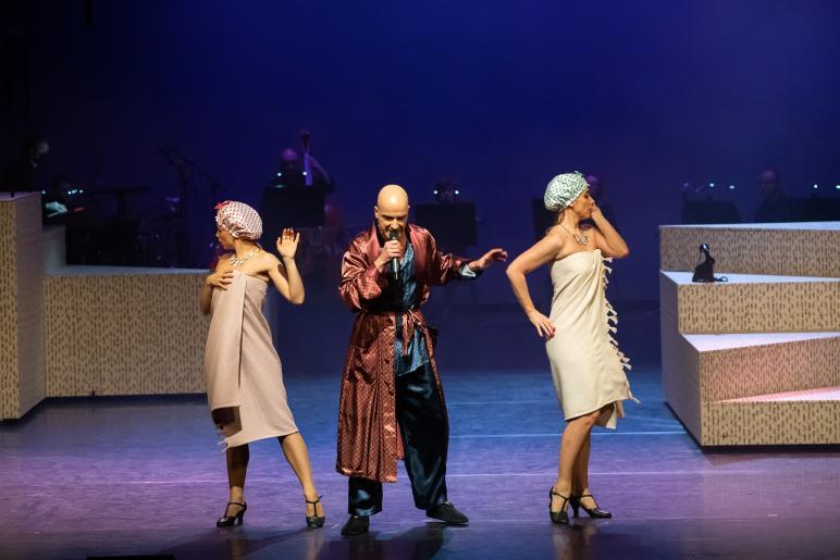 Zdjęcie przedstawia dwie kobiety i śpiewającego mężczyznę. Mężczyzna stojący w środku trzyma mikrofon w ręku i jest ubrany w szlafrok. Kobiety stojące po bokach są owinięte w ręczniki z czepkami kąpielowymi na głowach. W tle widać zespół grający na instrumentach.