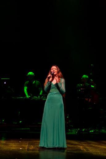Fotografia przedstawia śpiewającą solistkę ubraną w długą zieloną suknię. W tle widać zespół muzyczny grający na instrumentach.