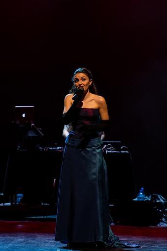 Fotografia przedstawia śpiewającą solistkę ubraną w długą ciemną suknię.