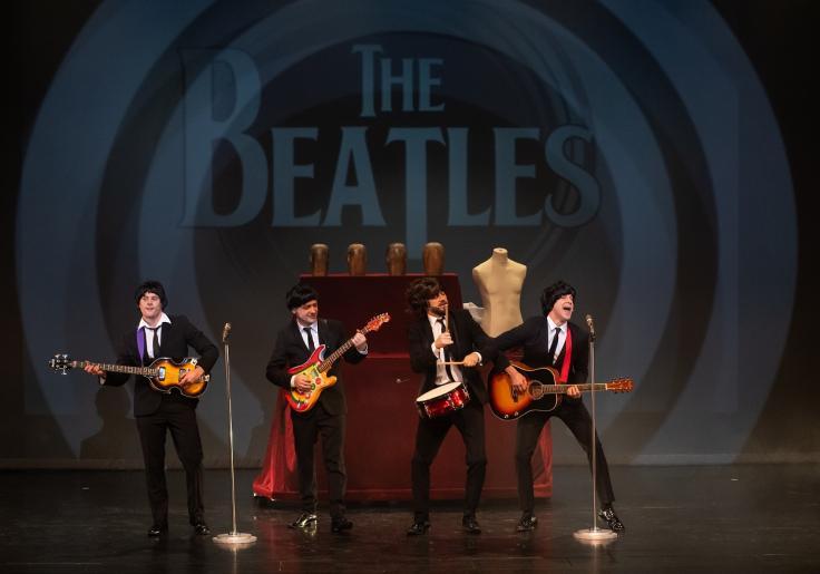 Na kolorowym zdjęciu widzimy trzech mężczyzn grających na gitarach i jednego na bębenku. Stylizowani są na Beatlesów, ubrani w czarne garnitury. Mężczyźni występują na scenie śpiewając do mikrofonów. W tle za nimi wyświetla się napis