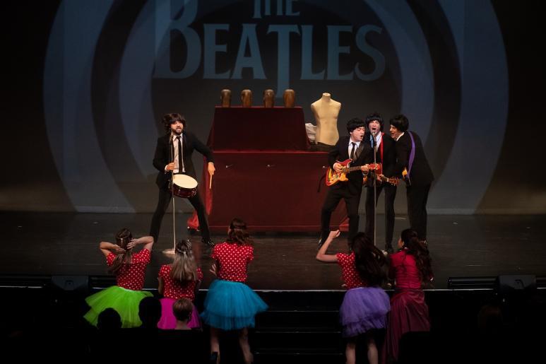 Na kolorowym zdjęciu widzimy trzech mężczyzn grających na gitarach i śpiewających do jednego mikrofonu, czwarty mężczyzna ekspresyjnie gra na bębenku. Mężczyźni stylizowani są na Beatlesów, ubrani w czarne garnitury.  W tle za nimi wyświetla się napis