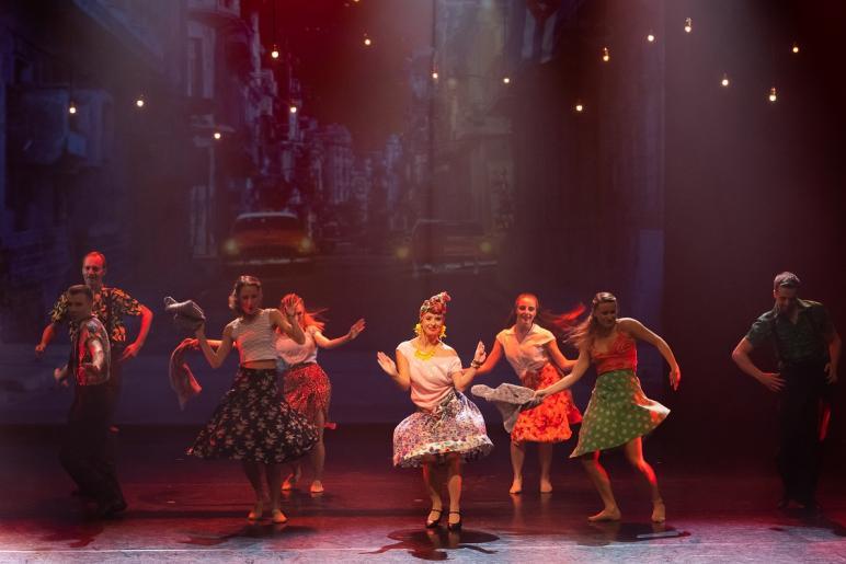 Na kolorowym zdjęciu widzimy 5 kobiet i 3 mężczyzn tańczących w grupie do kubańskich rytmów. Cała grupa ubrana jest w kolorowe i zwiewne ubrania. Kobiety maja na sobie rozkloszowane kolorowe spódnice i obcisłe bluzki, mężczyźni kolorowe koszule wpuszczone w spodnie z szelkami. W tle wyświetlają się jadące żółte taksówki po nocnych uliczkach Kuby.