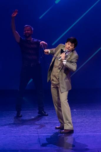 Na kolorowym zdjęciu widzimy dwóch mężczyzn. Jeden z nich jest stylizowany na Jerzego Połomskiego, ubrany w charakterystyczny dla piosenkarza garnitur. Drugi mężczyzna stoi za plecami pierwszego, i odgrywa rolę operatora mikrofonu. Zdjęcie ma humorystyczny wydźwięk ponieważ mężczyzna odgrywający Połomskiego jest wyraźnie splątany długim kablem od mikrofonu, natomiast drugi mężczyzna macha radośnie do publiczności.