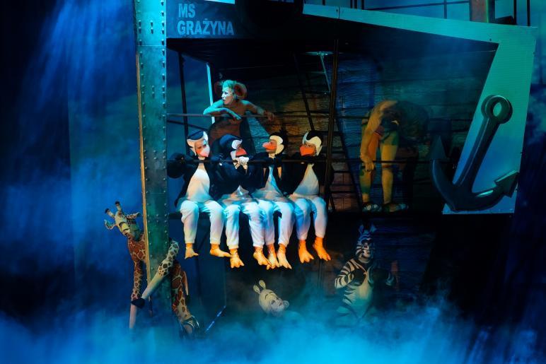 Na zdjęciu widzimy stenografię statku we wnętrzu którego, siedzi czterech aktorów odgrywających pingwiny. W tle widoczni są również aktorzy odgrywających rolę lwa żyrafy, hipopotamicy, zebry a także małpy.