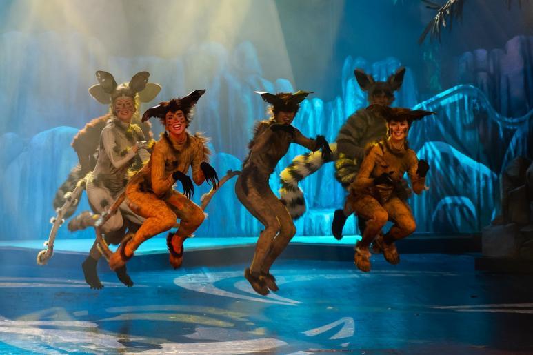 Fotografia przedstawia aktorów odrywających rolę lemurów. Aktorzy są roześmiani,  w widocznym podskoku.