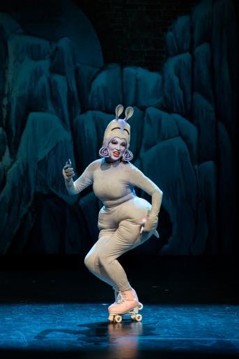 Fotografia przedstawia aktorkę wcielająca się w role  uśmiechniętej hipopotamicy jeżdżącej na wrotkach.