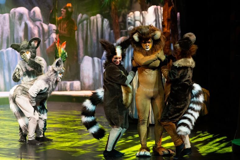 Fotografia przedstawia aktora odgrywającego rolę lwa, w otoczeniu roześmianych aktorów odgrywających lemury.