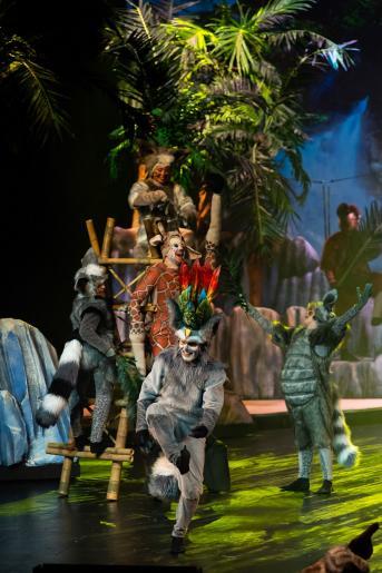 Fotografia przedstawia roześmianych  aktorów odgrywających lemury i żyrafę. Scenografia przedstawia dżunglę.